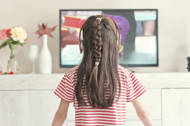 Rear view of little girl with headphones watching television