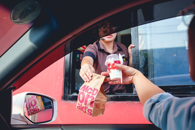 방콕, 태국-2017 년 3 월 4 일 : 주문 후 햄버거와 아이스크림을받은 미확인 고객, McDonald 's 드라이브 스루 서비스에서 구매, McDonald 's는 미국 패스트 푸드 레스토랑 체인입니다.