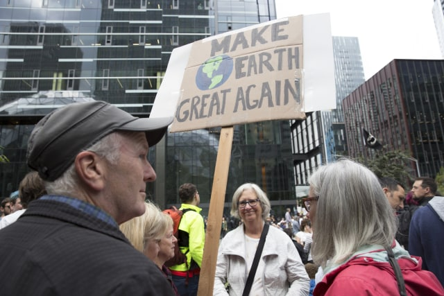 Former Amazon worker Clyde McQueen, left, holds a sign as Amazon Employees for Climate Justice lead a walk out and rally at the company's headquarters to demand that leaders take action on climate change in Seattle, Washington on September 20, 2019. (Photo by Jason Redmond / AFP)        (Photo credit should read JASON REDMOND/AFP via Getty Images)