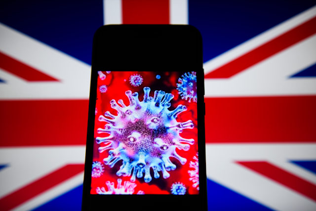 POLAND - 2020/04/10: In this photo illustration a COVID- 19 sample is seen displayed on a smartphone with the United Kingdom flag on the background. (Photo Illustration by Omar Marques/SOPA Images/LightRocket via Getty Images)