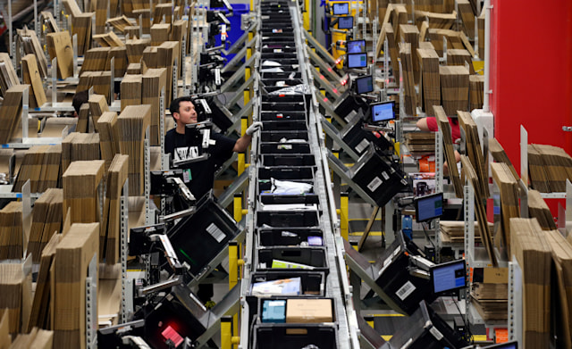 Workers process purchased orders at a packaging area inside Amazon distribution center in El Prat de Llobregat, near Barcelona, Spain, March 15, 2018. REUTERS/Albert Gea     TPX IMAGES OF THE DAY