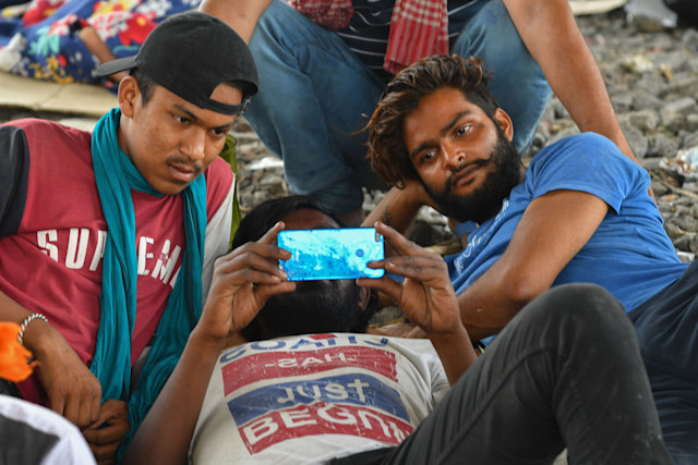 Migrant labourers watch a movie on their mobile phone while resting under a bridge during a government-imposed nationwide lockdown as a preventive measure against the spread of the COVID-19 coronavirus, in Mumbai on April 16, 2020. (Photo by INDRANIL MUKHERJEE / AFP) (Photo by INDRANIL MUKHERJEE/AFP via Getty Images)