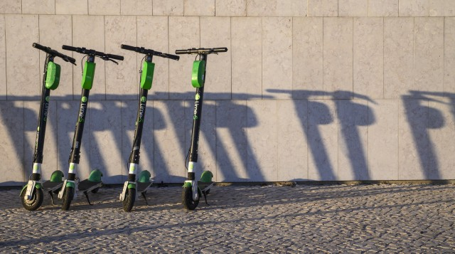 LISBON, PORTUGAL - JANUARY 13: A number of Lime-S e-scooters are parked in a neat row outside MAAT museum by the Tagus River on January 13, 2020 in Lisbon, Portugal. Since their introduction in Lisbon, e-scooters have become very popular with tourists and locals, but have also generated accidents and adverse reactions among the residents. Police are taking action against drivers who do not comply with safety regulations such as driving in pairs or not wearing helmets for accidents related to the use of these vehicles are on the rise. (Photo by Horacio Villalobos#Corbis/Corbis via Getty Images)