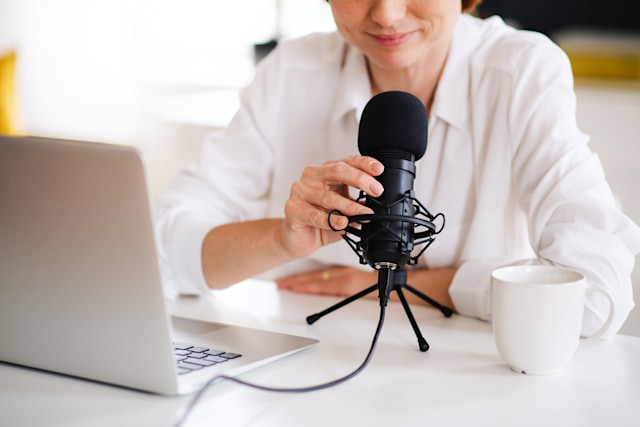 Female podcaster sitting at the table, talking on camera.