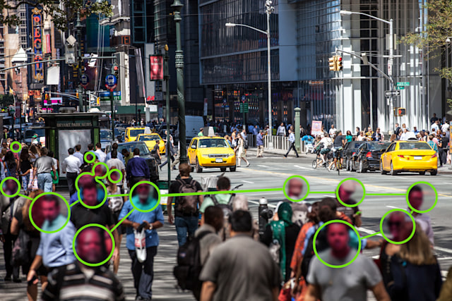 Facial Recognition technology used to prevent Covid-19 spread.  Note for inspectors: people is a crowd, cars are edited even if not necessary.
