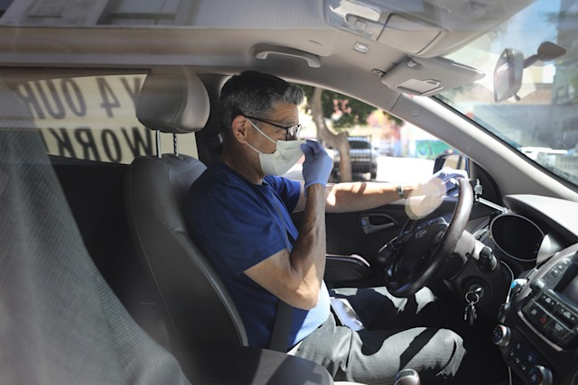 LOS ANGELES, CALIFORNIA - APRIL 16: A driver adjusts his face mask as Uber and Lyft drivers with Rideshare Drivers United and the? Transport Workers Union of America conduct a 'caravan protest' outside the California Labor Commissioner's office amidst the coronavirus pandemic on April 16, 2020 in Los Angeles, California. The drivers called for California to enforce the AB 5 law so that they may qualify for unemployment insurance as the spread of COVID-19 continues. Drivers also called for receiving back wages they say they are owed. (Photo by Mario Tama/Getty Images)