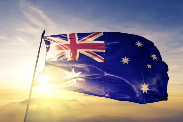 Australia Australian flag on flagpole textile cloth fabric waving on the top sunrise mist fog