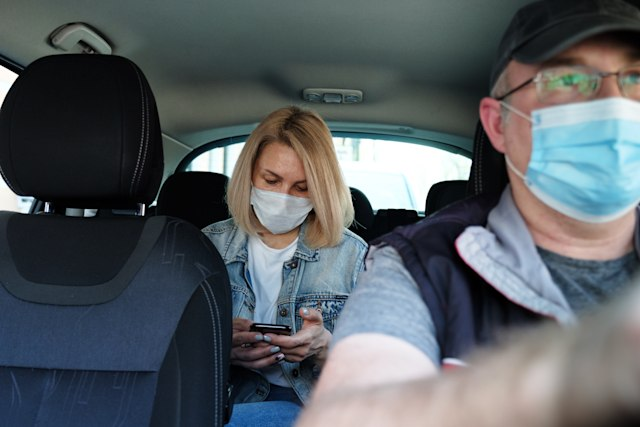 Caucasian woman in taxi wearing face mask for protection from pollution and viruses such as Coronavirus. Using smartphone
