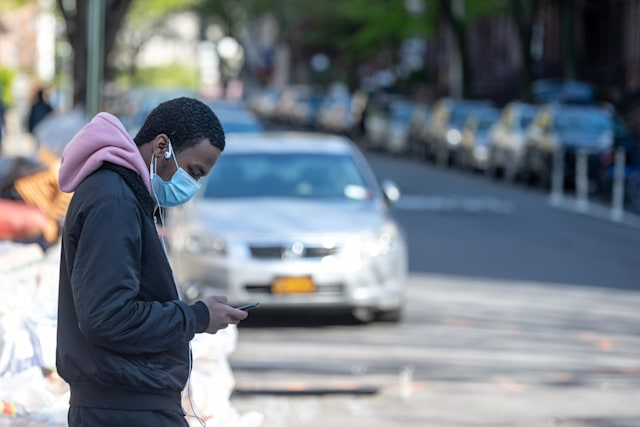 NEW YORK, NEW YORK - APRIL 28: A man wearing a protective mask looks at his iPhone amid the coronavirus pandemic on April 28, 2020 in New York City, New York. COVID-19 has spread to most countries around the world, claiming over 217,000 lives with over 3.1 million cases (Photo by Alexi Rosenfeld/Getty Images)