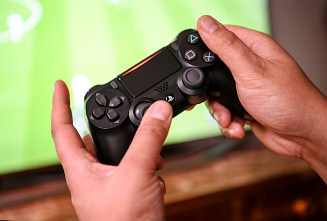 02 April 2020, Berlin: A young man plays with the game console Playstation 4. to prevent infection with the corona virus, many people spend their free time at home. Photo: Britta Pedersen/dpa-Zentralbild/dpa (Photo by Britta Pedersen/picture alliance via Getty Images)