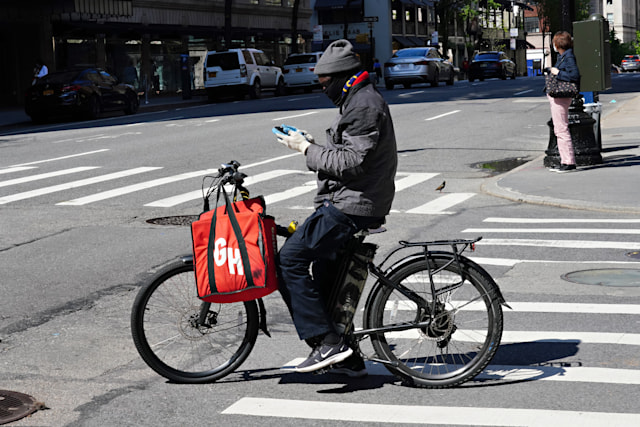 NEW YORK, NY - MAY 03: A Grubhub delivery person checks his phone during the coronavirus pandemic on May 3, 2020 in New York City. COVID-19 has spread to most countries around the world, claiming over 247,000 lives with over 3.5 million infections reported. (Photo by Cindy Ord/Getty Images)