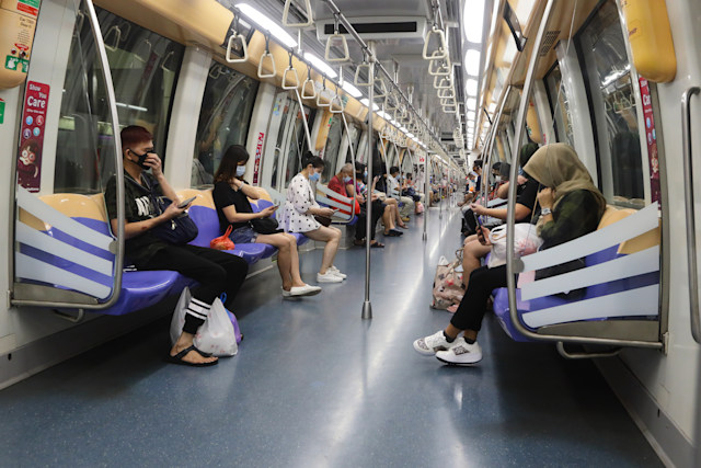 SINGAPORE - JUNE 02:  Commuters wearing protective mask ride the train on June 2, 2020 in Singapore. The authority decided to remove all safe distancing stickers and markers from trains and buses as they deemed it is too challenging for commuters to keep their social distance. Today, Singapore embarks on phase one of a three phase approach against the coronavirus (COVID-19) pandemic as it begins to ease the partial lockdown measures by allowing the safe re-opening of economic activities which do not pose high risk of transmission. This include the resumption of selected health services, re-opening of schools with school children attending schools on rotational basis, manufacturing and production facilities, construction sites that adhere to safety measures, finance and information services that do not require interactions and places of worship, amongst others. Retail outlets, social and entertainment activities will remain closed and dining in at food and beverage outlets will still be disallowed. The government will further ease restriction by the middle of June if the infection rate within the community remains low over the next two weeks.(Photo by Suhaimi Abdullah/Getty Images)