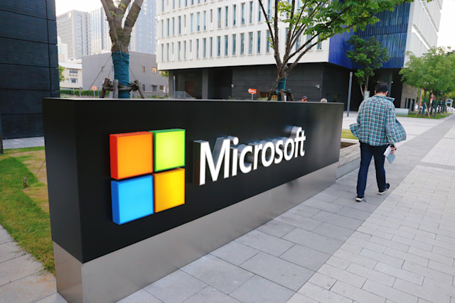 SHANGHAI, CHINA - JUNE 06: A man walks past a logo of Microsoft outside an office building at Shanghai Caohejing Hi-Tech Park on June 6, 2020 in Shanghai, China. (Photo by Chen Yuyu/VCG via Getty Images)