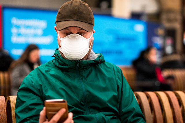 Close up color image depicting a young caucasian man in his 30s wearing a white protective face mask - to protect himself from flu viruses and the coronavirus - sitting and waiting on a bench at a railroad station in the city of London. He is wearing casual clothing, a green rainmack and messenger bag. In the background other people are defocused.