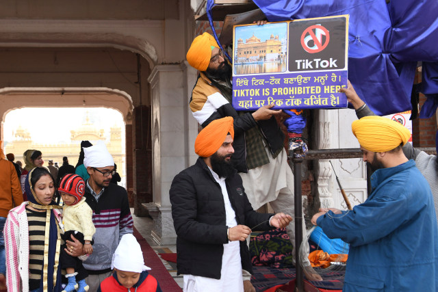 Sikh volunteers hangs a board reading 'Tiktok is prohibited here' at the Golden Temple in Amritsar on February 10, 2020. (Photo by NARINDER NANU / AFP) (Photo by NARINDER NANU/AFP via Getty Images)