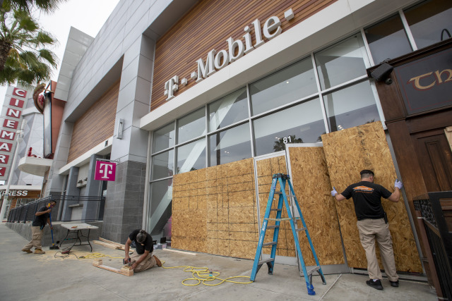 LONG BEACH, CA - JUNE 01:  After rioters looted, destroyed and burned businesses along Pine Ave. Sunday evening, workers replace broken glass at a T-Mobile store with plywood Monday, June 1, 2020 in Long Beach, CA.  (Allen J. Schaben / Los Angeles Times via Getty Images)