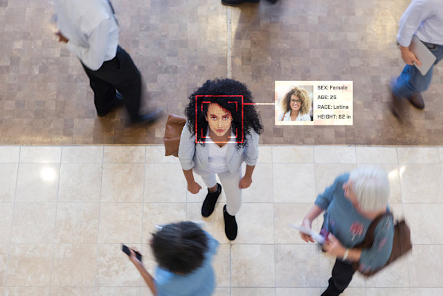 A young Hispanic businesswoman looks up while in an office lobby with businesspeople all around her. A facial recognition scan reveal her personal data.