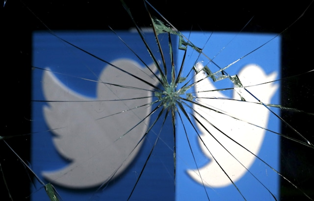 A 3D-printed Twitter logo is seen through broken glass, in this picture illustration taken February 8, 2016. Twitter shed 5.4 percent to hit a new record low of $14.87 after reports over the weekend that the company was planning to change how it display tweets.    REUTERS/Dado Ruvic/Illustration
