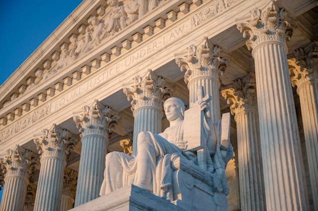 Sunset glow illuminated statue and colonnade of US Supreme court in Washington DC< USA