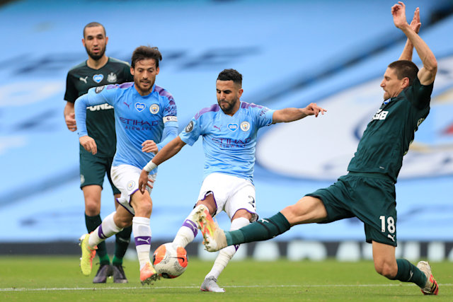 MANCHESTER, ENGLAND - JULY 08: Riyad Mahrez of Man City shoots as Federico Fernandez of Newcastle lunges in to challenge during the Premier League match between Manchester City and Newcastle United at Etihad Stadium on July 8, 2020 in Manchester, United Kingdom. (Photo by Simon Stacpoole/Offside/Offside via Getty Images)