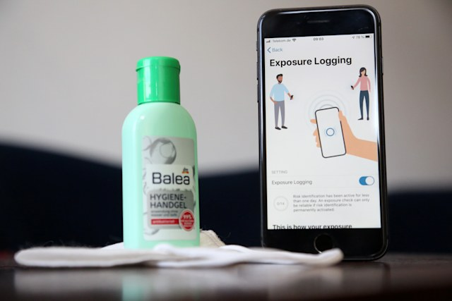 BERLIN, GERMANY - JUNE 16: The English version of the German federal health ministry's Corona-Warn-App software is seen on an Apple iPhone next to a medical facial mask and a bottle of hand sanitizer in this photo illustration on the day of the app's release during the novel coronavirus pandemic on June 16, 2020 in Berlin, Germany. Germany launched its contact tracing smartphone app, which uses short-range Bluetooth to alert people who may have been exposed to an individual who has contracted the coronavirus, without relying on a centralized database. The app was originally scheduled for launch in April, but was delayed due to technical difficulties and concerns over privacy issues. (Photo by Adam Berry/Getty Images)