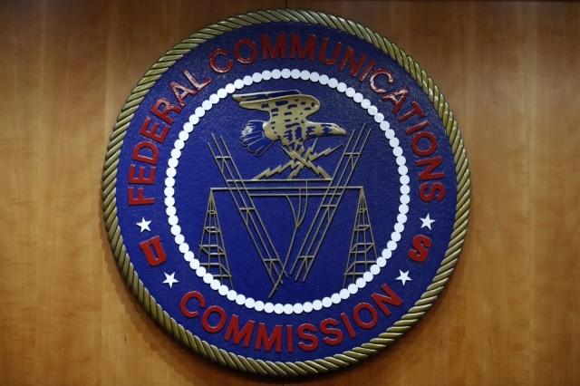 The seal of the Federal Communications Commission (FCC) is seen before an FCC meeting to vote on net neutrality in Washington, Thursday, Dec. 14, 2017. (AP Photo/Jacquelyn Martin)