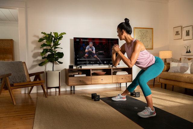 A person works out at home using the Peloton app.