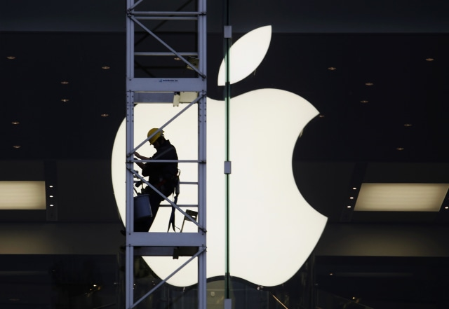 A worker climbs outside an Apple store in Hong Kong April 10, 2013. Apple apologised to Chinese consumers last Monday and altered iPhone warranty policies in its No. 2 market after more than two weeks of condemnation in the state-run media of its after-sales service. With its rare apology, Apple Inc went from pariah to praiseworthy in the eyes of China's state-controlled media, a lesson for other foreign firms not to underestimate the speed and power of the government press.   REUTERS/Bobby Yip (CHINA - Tags: BUSINESS SCIENCE TECHNOLOGY SOCIETY TPX IMAGES OF THE DAY)