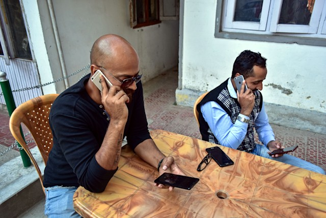 KASHMIR, JAMMU & KASHMIR, INDIA - 2019/10/14: Men talk on a mobile phones after communication being restored in Kashmir. Postpaid mobile phone services have been restored on the state-run BSNL Network in Kashmir Valley after over 72 days of the lock down in Jammu and Kashmir. (Photo by Saqib Majeed/SOPA Images/LightRocket via Getty Images)