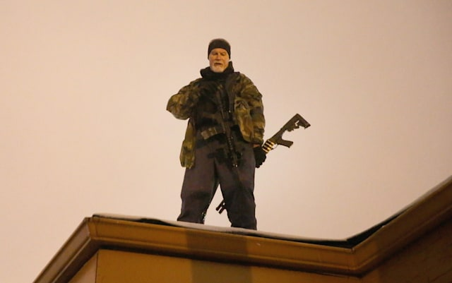 FERGUSON, MO - NOVEMBER 26:  John Karriman. a volunteer from Oath Keepers, stands guard on the rooftop of a  business on November 26, 2014 in Ferguson, Missouri. Demonstrators looted and burned down several businesses along the street on Monday after the grand jury announced its decision in the Michael Brown case. Brown, an 18-year-old black man, was killed by Darren Wilson, a white Ferguson police officer, on August 9. (Photo by Scott Olson/Getty Images)