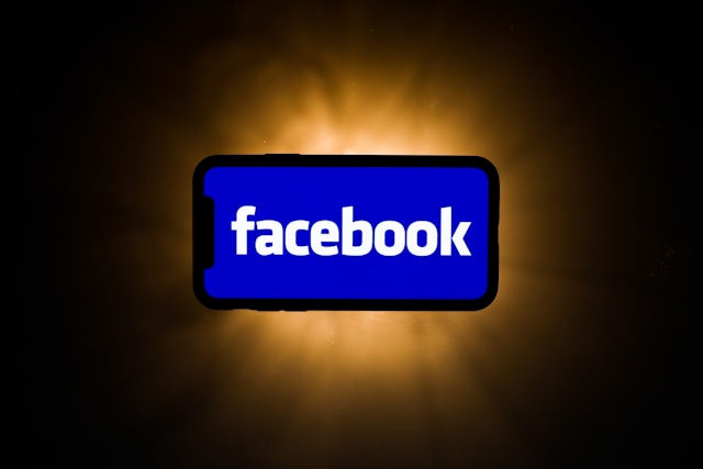 Facebook logo is seen displayed on phone screen in this illustration photo taken in Poland on July 23, 2020. Messenger, developed by Facebook, has introduced feature called Rooms that allows group video chats. Video meeting apps gained popularity during the coronavirus pandemic.  (Photo illustration by Jakub Porzycki/NurPhoto via Getty Images)