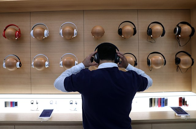 "SAN FRANCISCO, CA - MAY 19:  An Apple Store employee tries on a pair of headphones during a press preview of the new flagship Apple Store on May 19, 2016 in San Francisco, California. Apple is preparing to open its newest flagship store in San Francisco's Union Square on Saturday May 21. The new store features new design elements as well as community programs including the ""genius grove"" where where customers can get support under a canopy of local trees and ""the plaza"" a public space that will be open 24 hour a day. Visitors will enter the store through 42-foot tall sliding glass doors.  (Photo by Justin Sullivan/Getty Images)"