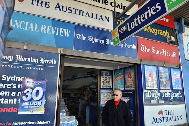 A man leaves a newsagency shop in Sydney on September 14, 2017.  Controversial changes to Australia's media laws neared agreement on September 14, 2017 in a deal likely to result in significant concentration of ownership, but also a probe into the impact of platforms like Google and Facebook on the industry. / AFP PHOTO / PETER PARKS        (Photo credit should read PETER PARKS/AFP via Getty Images)