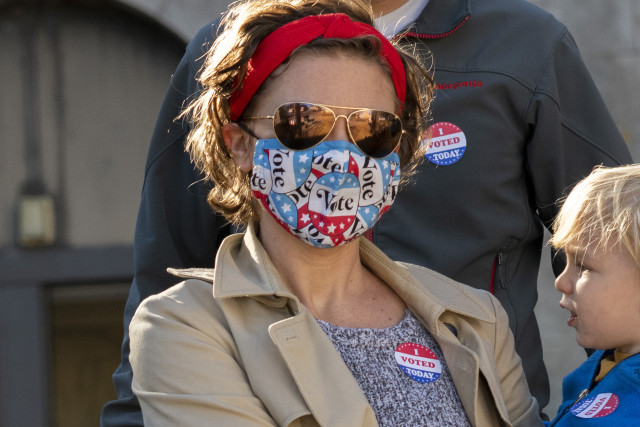 "PHILADELPHIA, PA - OCTOBER 17:  Nya Nelson wears a ""Vote"" themed mask due to the coronavirus pandemic and an ""I VOTED TODAY"" sticker while departing with her family after casting their early voting ballots at Roxborough High School on October 17, 2020 in Philadelphia, Pennsylvania.  With the election only a little more than two weeks away, a new form of in-person early voting by using mail ballots, enables millions of voters have already cast their ballots.  President Donald Trump won the battleground state of Pennsylvania by only 44,000 votes in 2016, the first Republican to do so since President George Bush in 1988.  (Photo by Mark Makela/Getty Images)"