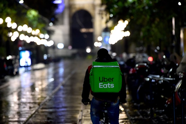 MILAN, ITALY - OCTOBER 26:  A Uber Eats food delivery rider rides along a street in Corso Sempione on October 26, 2020 in Milan, Italy. To combat a second wave of COVID-19 cases, Italy introduced new restrictions, including the 6pm closure of bars and restaurants and complete closure of gyms, swimming pools, cinemas, theatres and ski stations.  (Photo by Pier Marco Tacca/Getty Images)