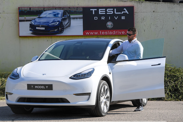 "A picture taken on September 5, 2020 shows a driver testing a ""Tesla Model Y"" car, an all-electric compact SUV by US electric car giant Tesla, during its presentation at the Automobile Club in Budapest. (Photo by ATTILA KISBENEDEK / AFP) (Photo by ATTILA KISBENEDEK/AFP via Getty Images)"