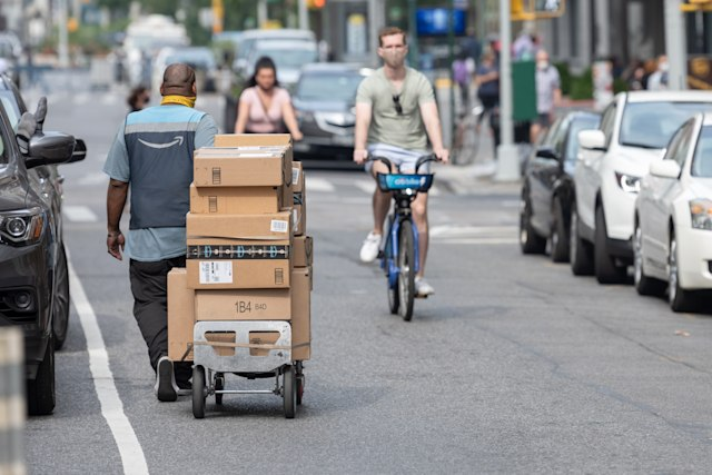 NEW YORK, NEW YORK - SEPTEMBER 25: An Amazon Prime delivery person wheels a hand cart with Amazon packages as the city continues Phase 4 of re-opening following restrictions imposed to slow the spread of coronavirus on September 25, 2020 in New York City. The fourth phase allows outdoor arts and entertainment, sporting events without fans and media production.  (Photo by Alexi Rosenfeld/Getty Images)