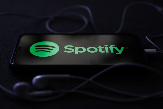 Spotify logo displayed on a phone screen and headphones are seen in this illustration photo taken in Poland on October 18, 2020.   (Photo Illustration by Jakub Porzycki/NurPhoto via Getty Images)