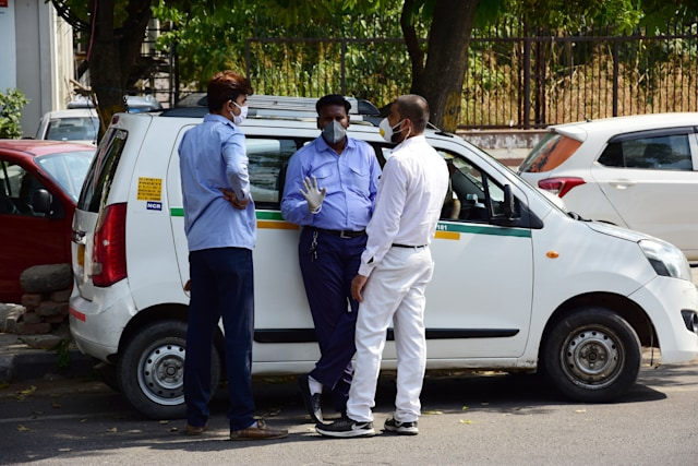 DELHI, INDIA - 2020/05/19: Cab drivers (ola,Uber) chatting on the road side while wearing face masks as a precaution, during the eased lockdown restrictions. As a preventive measure against the spread of the COVID-19, restrictions were imposed, the govt has eased some of the restrictions after several days of lockdown. (Photo by Manish Rajput/SOPA Images/LightRocket via Getty Images)