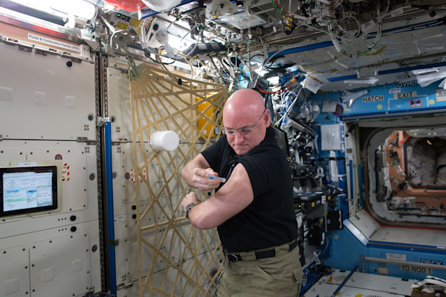 IN SPACE - SEPTEMBER 24:  In this handout photo provided by NASA, NASA astronaut Scott Kelly gives himself a flu shot for an ongoing study on the human immune system September 24, 2015 in space. The vaccination is part of NASA's Twins Study, a compilation of multiple investigations that take advantage of a unique opportunity to study identical twin astronauts Scott and Mark Kelly, while Scott spends a year aboard the International Space Station and Mark remains on Earth. (Photo by NASA via Getty Images)