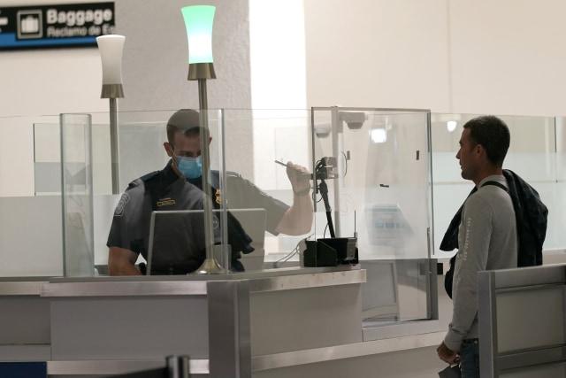Penumpang internasional tiba di Bandara Internasional Miami di mana mereka diperiksa oleh Bea Cukai dan Perlindungan Perbatasan (CBP) A.S. menggunakan biometrik wajah untuk mengotomatiskan pemeriksaan dokumen manual yang diperlukan untuk masuk ke A.S. Jumat, 20 November 2020, di Miami. Bandara Internasional Miami adalah bandara terbaru yang menyediakan Bandara Kedatangan Sederhana di seluruh bandara. (Foto AP / Lynne Sladky)