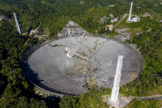 This aerial view shows the damage at the Arecibo Observatory after one of the main cables holding the receiver broke in Arecibo, Puerto Rico, on December 1, 2020. - The radio telescope in Puerto Rico, which once starred in a James Bond film, collapsed Tuesday when its 900-ton receiver platform fell 450 feet (140 meters) and smashed onto the radio dish below. (Photo by Ricardo ARDUENGO / AFP) (Photo by RICARDO ARDUENGO/AFP via Getty Images)