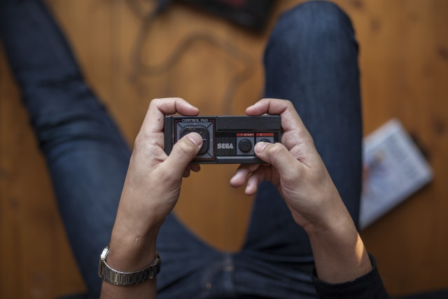 Gothenburg, Sweden - January 07, 2015: A shot from above of a young mans hands holding an old game pad for the Sega Master System. Natural lights.