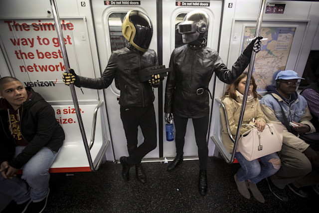 A couple dressed up as musical act Daft Punk ride the shuttle subway at Times Square station in the Manhattan borough of New York, October 31, 2015.   REUTERS/Carlo Allegri      TPX IMAGES OF THE DAY