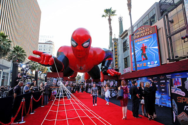 An inflatable spider-man hovers over the red carpet of a film premiere.