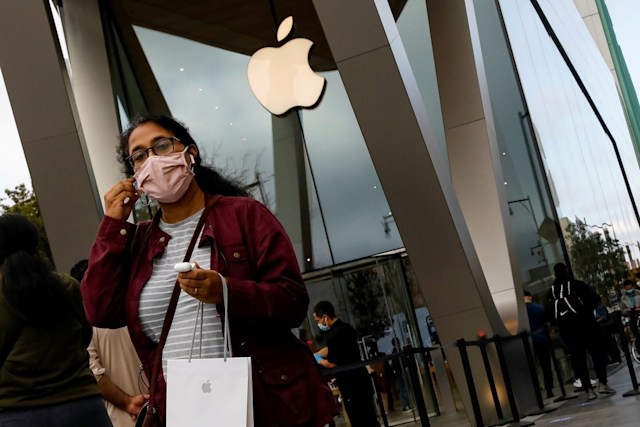 A customer exits after picking up Apple's new 5G iPhone 12 that went on sale, as the coronavirus disease (COVID-19) outbreak continues, at an Apple Store in Brooklyn, New York, U.S. October 23, 2020.  REUTERS/Brendan McDermid