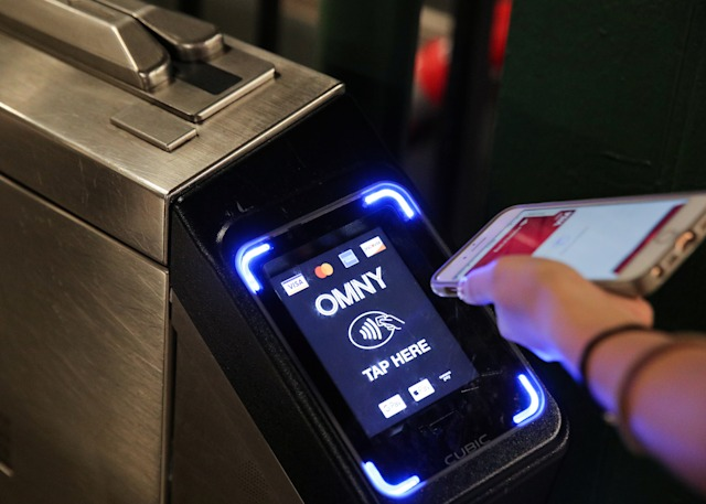 A customer uses a phone to pay for a New York City subway ride on the first day of operation of the OMNY (One Metro NY) contactless payment system in New York, U.S., May 31, 2019. REUTERS/Brendan McDermid
