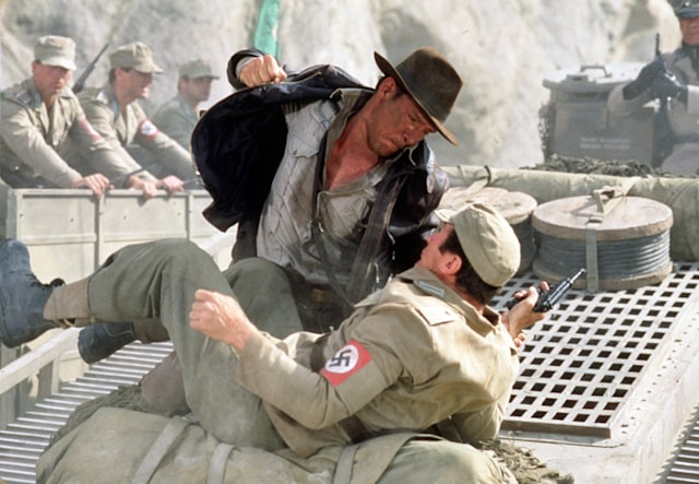 American actor Harrison Ford as the eponymous archaeologist in a scene from the film 'Indiana Jones and the Last Crusade', 1989. Here, he has a fistfight with a German soldier atop a moving tank. (Photo by Murray Close/Getty Images)