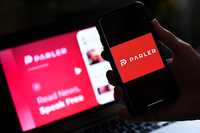 """This illustration picture shows social media application logo from Parler displayed on a smartphone with its website in the background in Arlington, Virginia on July 2, 2020. - Amid rising turmoil in social media, recently formed social network Parler is gaining with prominent political conservatives who claim their voices are being silenced by Silicon Valley giants. Parler, founded in Nevada in 2018, bills itself as an alternative to """"ideological suppression"""" at other social networks. (Photo by Olivier DOULIERY / AFP) (Photo by OLIVIER DOULIERY/AFP via Getty Images)"""