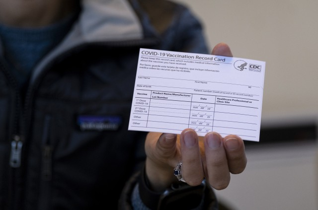 Sarah Gonzalez of New York, a Nurse Practitioner, displays a COVID-19 vaccine card at a New York Health and Hospitals vaccine clinic in the Brooklyn borough of New York Sunday, Jan. 10, 2021. The clinic, serving 30 people getting vaccines Sunday, will expand to a twenty four hour, seven days a week operation starting Monday. (AP Photo/Craig Ruttle)